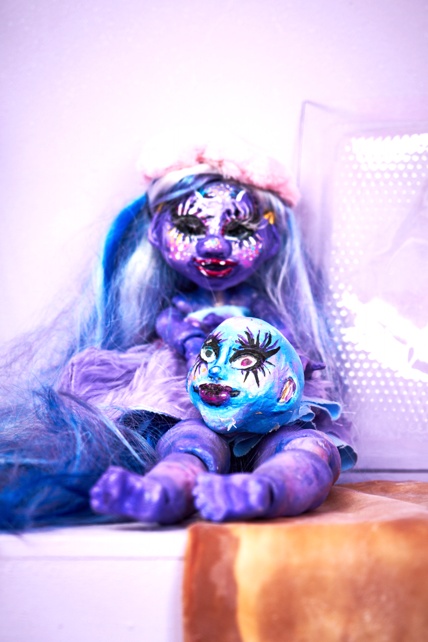 A ball jointed doll (BJD doll) painted in different purple tones. blue long hair. Sitting in the toy store installation.