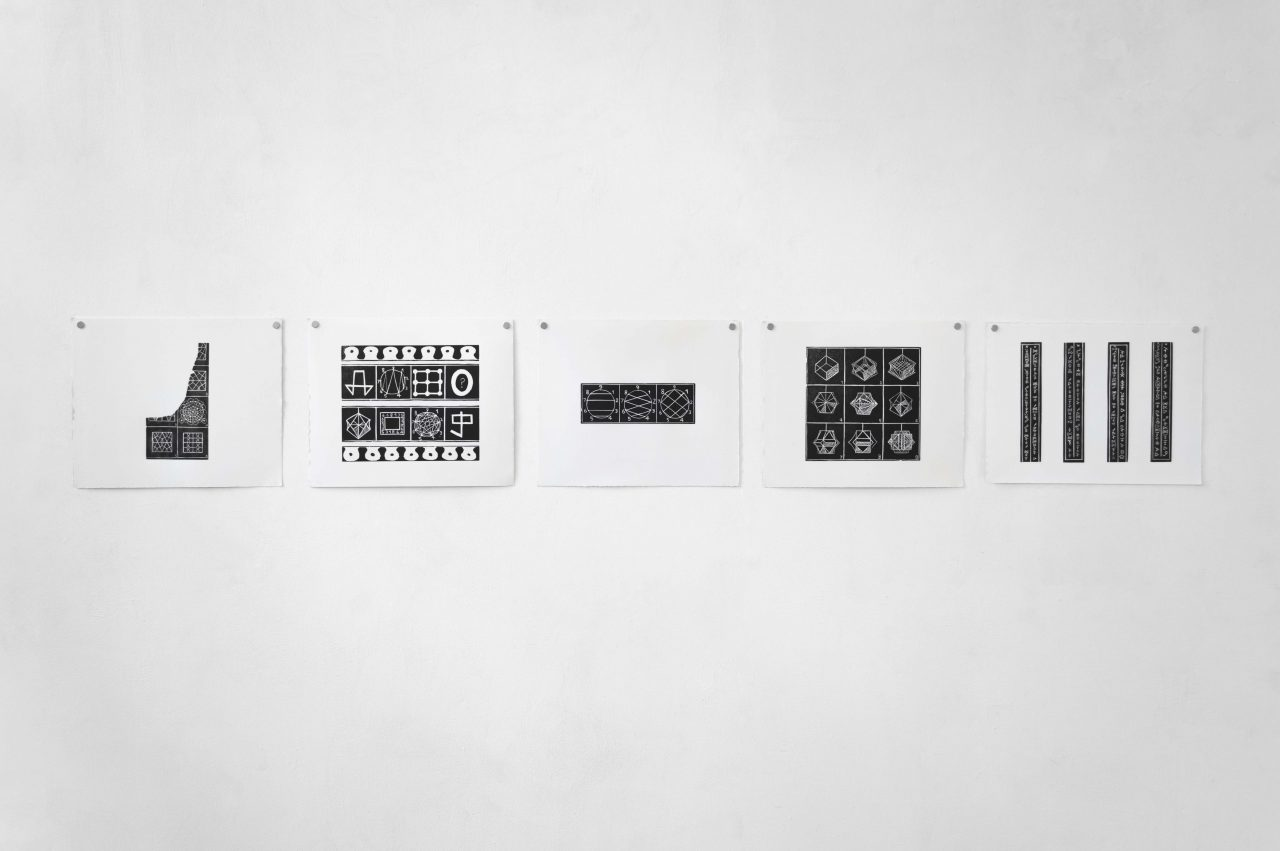 A series of 5 lino prints in landscape orientation hung on a white wall with silver magnets in the top two corners. The black and white prints display fragments of diagrams, repeated geometric patterns and numbered sequences.