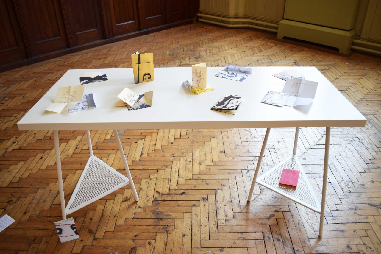 Laid out letter of I Installation of books, letters, and envelopes into space, supported by a table and surrounding wall.