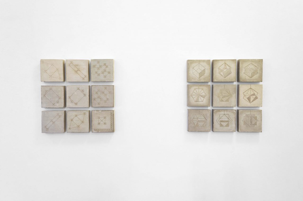 An installation shot of 12 concrete square sculptures hung on a white wall in two sets of 9 square grids. On each of the squares surface is a laser engraved pattern, such as geometric shapes, star patterns and numbers.