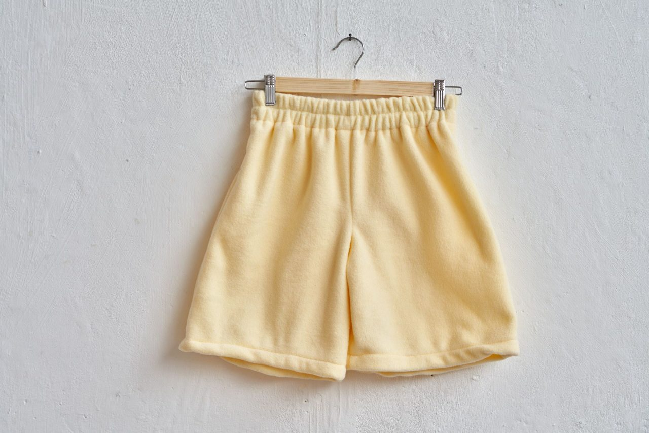 yellow fleece jogger shorts made from my own pattern hanging on a wall