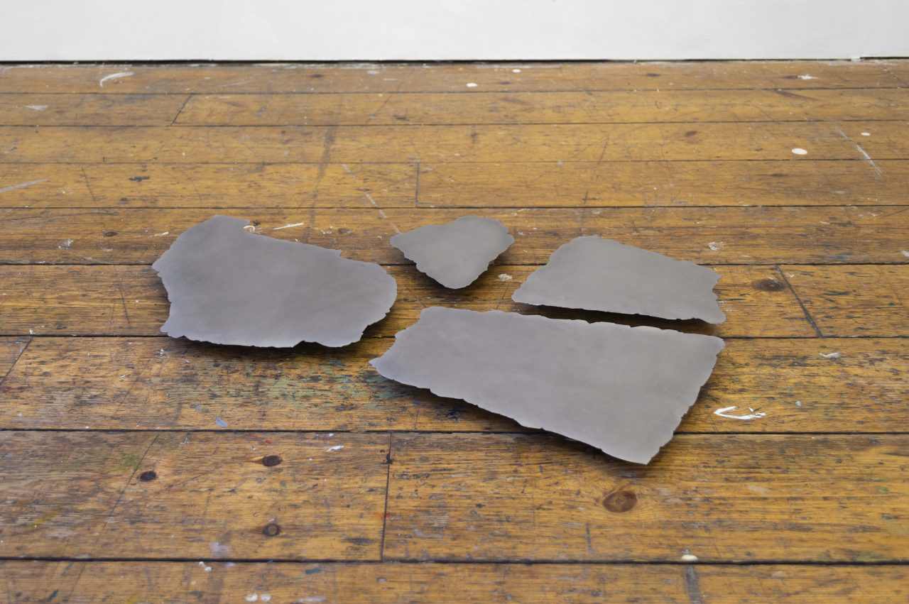 A gallery installation shot of a floor sculpture consisting of 4 polished sheets of steel that has been cut into natural rock lock forms. The sheets appear to float a few cm off of the ground, casting a small shadow below.